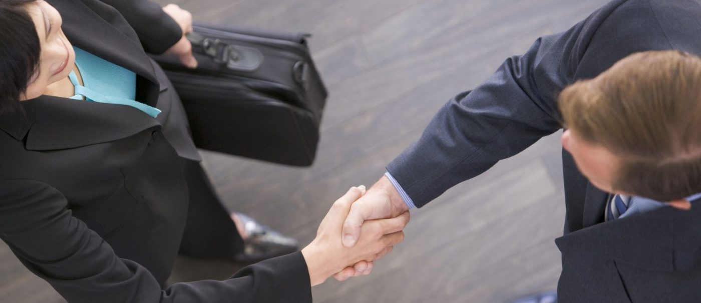 Two Businesspeople Standing Indoors Shaking Hands
